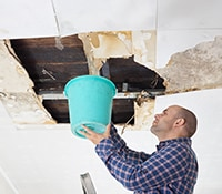 Man Checking for Leaks in Basement Ceiling